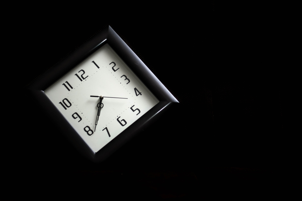 A black clock with a white face hangs diagonally in darkness. The hands read thirty eight past seven o'clock.