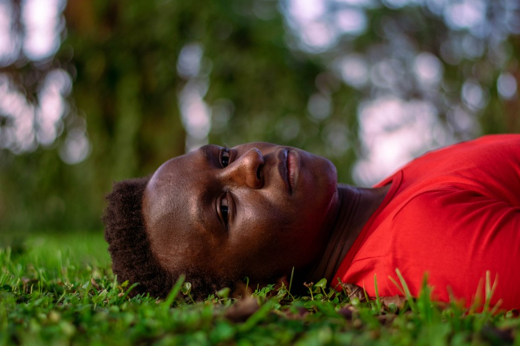 A handsome lad lays on short grass facing the camera. He is wearing a red Supreme gym shirt and has a long black afro. His eyes are forlorn.